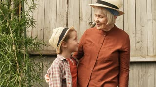 PAN of happy senior woman and little girl wearing straw hats standing against wooden door in garden and looking at each other, then turning towards camera and smiling