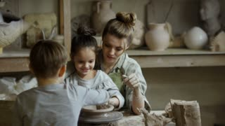 PAN of happy young woman and cute little children making earthenware on spinning pottery wheel in workshop