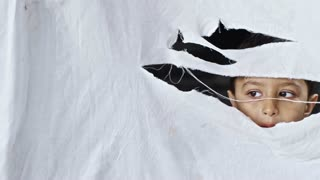 PAN of little Arab boy standing behind torn cloth with stains and looking through hole