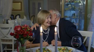 PAN of loving elderly couple flirting and hugging during romantic date in restaurant