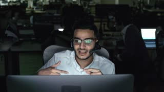 PAN of male Arab helpdesk worker in glasses gesturing and talking on headset while helping client