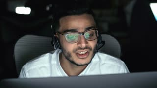 PAN of male Arab technical support worker looking at computer screen and talking on headset with customer having problems