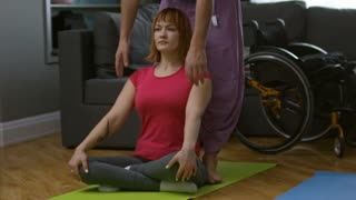 PAN of male instructor helping paraplegic woman to do yoga poses at home; wheelchair standing in background