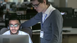 PAN of male manager in glasses explaining something to Arab telemarketing agent in headset working on computer; name on badge is used in fictitious manner