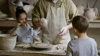 PAN of male potter wearing apron putting piece of clay on pottery wheel and wetting it with sponge while teaching curious children in his workshop
