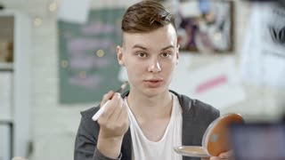 PAN of male teenage beauty guru sitting before video camera and talking while filming himself applying foundation wit brush