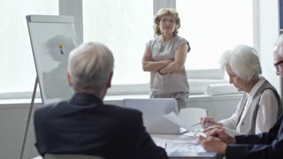 PAN of mature businesswoman in glasses standing beside whiteboard and talking to team of elderly businesspeople with grey hair while having meeting in office