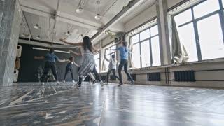 PAN of multiethnic group of happy women dancing zumba in studio and having fun