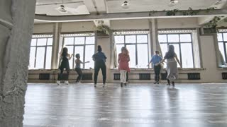 PAN of multiethnic group of young women laughing and dancing zumba in studio