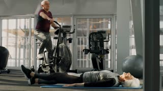 PAN of muscly senior man training on cycling machine as elderly woman lying on mat and doing fitness in gym