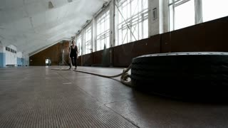 PAN of muscly sportswoman in fitness clothes gritting teach and pulling heavy tire by rope during cross-training workout in empty gymnasium