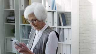 PAN of senior businesswoman with grey hair working on mobile phone in office