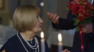 PAN of senior man gifting bouquet of red roses to happy elderly woman, then kissing her on cheek during romantic date in restaurant