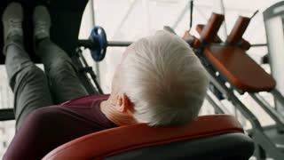 PAN of senior man with grey hair exercising on leg press machine in gym