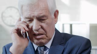 PAN of serious senior businessman in suit talking on mobile phone in office