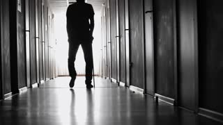 PAN of silhouette of limping man with stick slowly walking along dark hallway of hospital towards window with bright light
