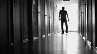 PAN of silhouette of man with walking stick limping along dark hallway of hospital towards camera