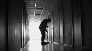 PAN of silhouette of unrecognizable male cleaner sweeping floor with broom in dark hallway