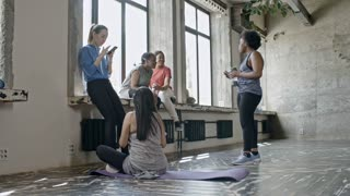 PAN of sporty women chatting and resting on windowsill after yoga class
