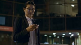 PAN of successful Asian businesswoman in glasses standing outdoors at night and looking at mobile phone, then getting into black taxi and driving away