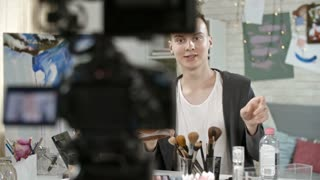 PAN of teenage boy sitting before video camera on tripod and filming himself applying makeup with brush and giving advice