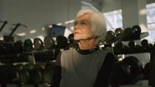 PAN of tired elderly woman with grey hair sitting by shelf with dumbbells in gym and drinking from sports water bottle