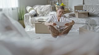 PAN of tired woman sitting on floor of new house and reading assembling manual, then looking at disassembled wooden furniture and thinking; sofa in plastic wrap and unpacked boxes in background