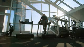 PAN of unrecognizable elderly man with grey hair running on treadmill in gym with panoramic windows