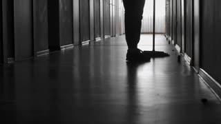 PAN of with low-section of unrecognizable janitor sweeping floor in dark corridor