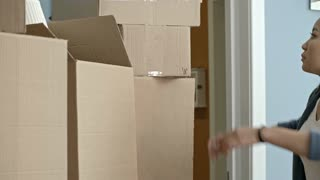 PAN of young Asian woman searching for something in cardboard box as her husband carrying rolled up carpet