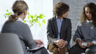 PAN of young female couple hugging and finding compromise during psychotherapist appointment