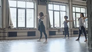 PAN of young female dance teacher with curly hair showing warming up exercises to multiethnic group of young women before class in studio