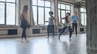 PAN of young female teacher with curly hair showing dance moves to multiethnic group of young women in class in airy studio