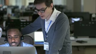 PAN of young woman and male supervisor looking at computer screen and discussing something as African call centre worker with headset listening and nodding