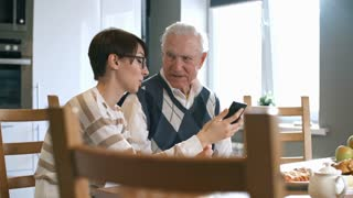 PAN of young woman in glasses sitting at kitchen table and teaching senior man how to use smartphone