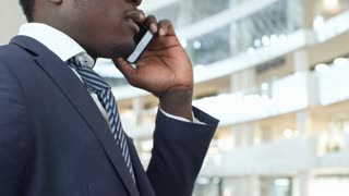 PAN shot of African American businessman in formal shirt and tie standing in the lobby of modern office center and talking on cell phone