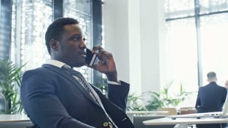 PAN shot of African American businessman in formal suit sitting at table with laptop on it and talking on mobile phone in coworking space