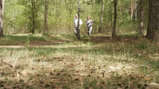 PAN shot of elderly woman and man running along forest trail in morning