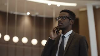 PAN shot of joyous African businessman standing in hotel lobby and talking on mobile phone