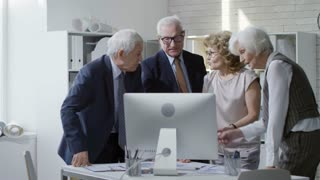 PAN shot of senior businesswomen and businessmen with grey hair standing looking at computer screen and disputing over work issues in office