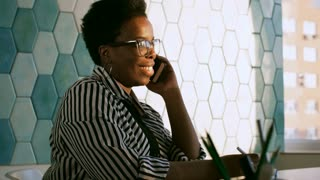 PAN shot of smiling african american businesswoman in eyeglasses writing on notepad and speaking on mobile phone in the office