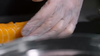 PAN with close up of unrecognizable cook in gloves cutting Philadelphia sushi rolls