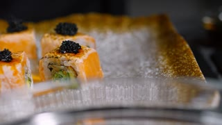 PAN with close up of unrecognizable cook in gloves putting colorful seaweed on plate with fresh sushi rolls
