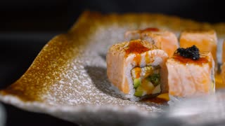 PAN with close up of unrecognizable cook wearing gloves putting black caviar on fresh sushi rolls