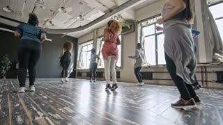 PAN with low angle of multiethnic group of young women dancing zumba in studio