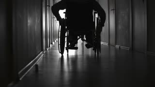 PAN with low angle of silhouettes of man riding wheelchair and male patient with limp walking along dark hospital corridor