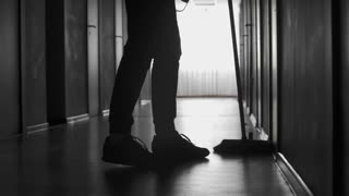 PAN with low-section of silhouette of legs of male janitor sweeping floor with broom in dark corridor