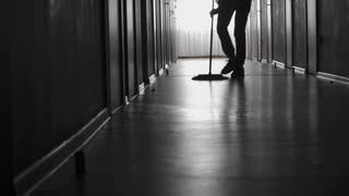 PAN with low-section of unrecognizable figure of male janitor sweeping floor in dark corridor