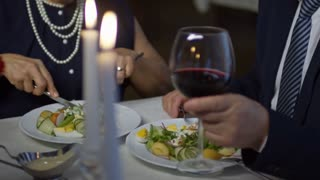 PAN with mid-section of senior couple eating salad and drinking wine while having romantic date in restaurant