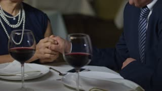 PAN with mid-section of unrecognizable elderly woman and man holding hands and talking on romantic date in restaurant